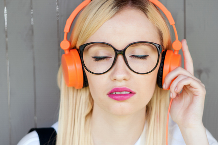 girl listening to music, girl enjoying music, relaxing, orange headphones, street shoot, music energy, lifestyle, european or american style, clear sound, sunshine, outdoors