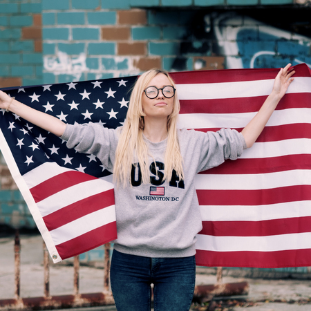 Adorable blonde girl posing with american flag