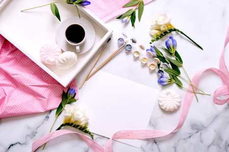 Womens desk. Flat lay, top view. Home office workspace. Creative feminine background. Coffee, marshmallows, , blue bouquet, pink fabric and pink ribbon.
