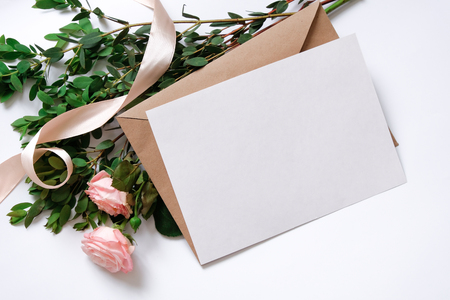 Mockup with postcard, flowers bouquet, kraft envelope. Overhead view. Flat lay, top view. Invitation card. Stock Photo
