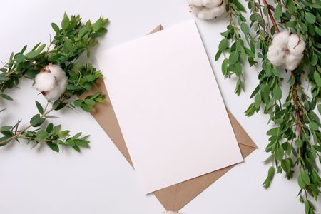 Kraft paper envelope with white card. Flat lay, top view, isolated on white background. Green leaves and cotton on the sides of the frame. Wedding invitation card.