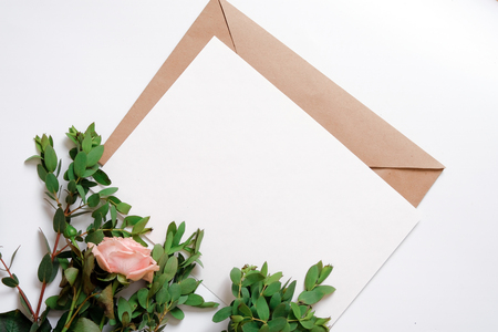 Kraft paper envelope with white card. Flat lay, top view, isolated on white background. Wedding invitation card.