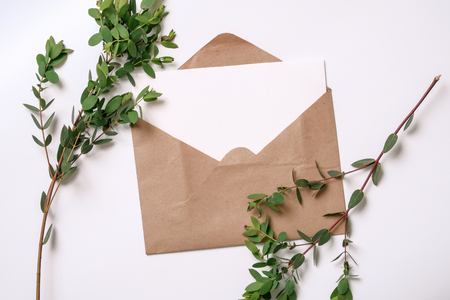 Kraft envelopes and green leaves on white background. Flat lay, top view invitation card. Overhead view. Isolated.