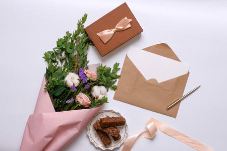 Mockup with postcard, flowers bouquet, kraft envelope and delicious wafers. Flat lay, top view.