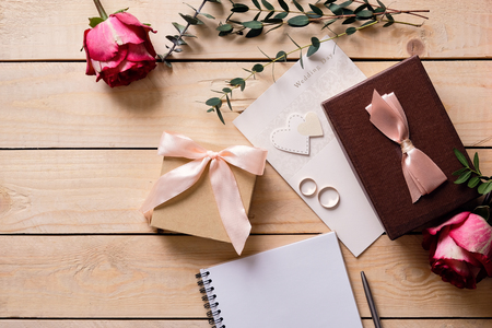 Wedding flat lay mock-up. Wedding invitation cards, red roses and green leaves, wedding rings. Overhead view, top view. Wooden background. Stock Photo