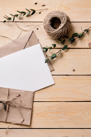 Top view of envelope and blank greeting card on white wooden background with vintage tone. Twine. Gift wrapping. Send a postcard. Handmade kraft gift cards.