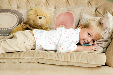 Child is lying on the sofa with a teddy bear. Stock Photo