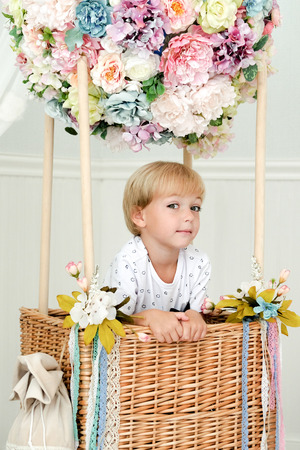 Young boy in decoratvie balloon of flowers