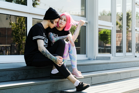 Couple in love. Beautiful young couple posing outdoor. Pink hair girl and hipster style