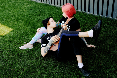 Couple in love. Portrait of redhead girl and hipster young boy lying on the grass