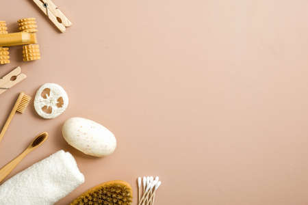 Natural bathroom accessories, organic spa and beauty treatment products on brown background. Zero waste, plastic free concept. Flat lay homemade soap, bamboo toothbrush, wooden pins, luffa sponge.