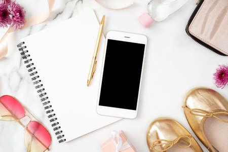 Flat lay home office desk. Female workspace with mobile phone, paper notepad, golden shoes and feminine accessories on marble background. Fashion blog banner. Beauty blogger desk concept. Top view.