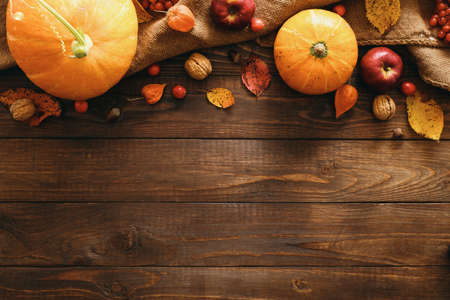 Autumn frame border made of pumpkins, blanket, dried fall leaves, apples, red berries, walnuts on wooden table. Thanksgiving, Halloween, Autumn Harvest concept. Flat lay composition, top view Stock Photo