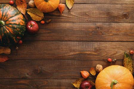 カボチャ、乾燥した紅葉、リンゴ、赤い果実、クルミ、木製のテーブルの上の毛布で作られた秋のフレーム。感謝祭、ハロウィーン、秋の収穫の概念。フラットレイコンポジション、トップビュー、コピースペース
