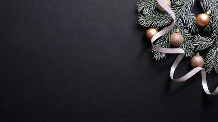 Christmas banner. Christmas tree branch decorated copper color balls and ribbon on black background. Flat lay, top view. Xmas banner mockup with copy space.