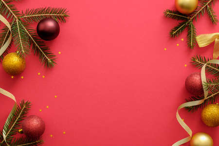 Christmas composition. Christmas frame made of fir three branches, gold and red decorations, ribbon on red background. Flat lay, top view. Christmas banner mockup template with copy space
