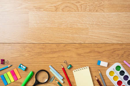 Background with bottom border made of stationery, school supplies on wooden table. Education, studying and back to school concept. Child desk top view, copy space, flat lay composition. Stock fotó