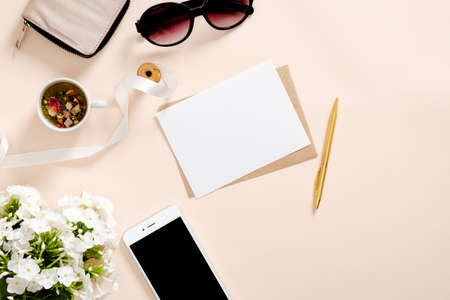 Flatlay composition with feminine accessories, blank paper card mockup, tea cup, smartphone, sunglasses, daisy flowers on pastel pink background. Feminine home office desk concept. Flat lay, top view