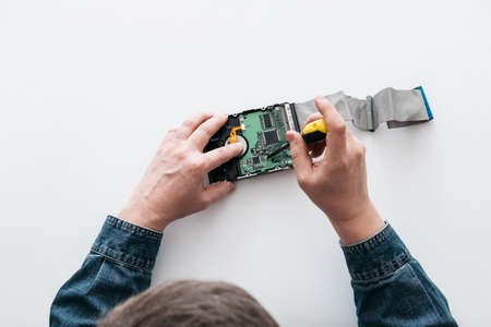 Hard disk recovery service, hands of repairman holding broken hdd with bad sectors. Computer engineer performs urgent repairs recovery of lost data during deletion HDD Imagens