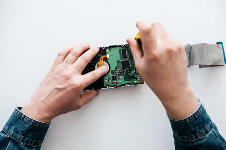 Hard disk recovery service, hands of repairman holding broken hdd with bad sectors. Computer engineer performs urgent repairs recovery of lost data during deletion HDD