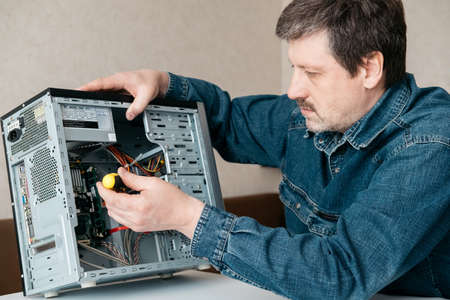 Computer technician engineer with screwdriver in his hand is repairing the personal computer. Concept of computer hardware, repairing, upgrade and technology.