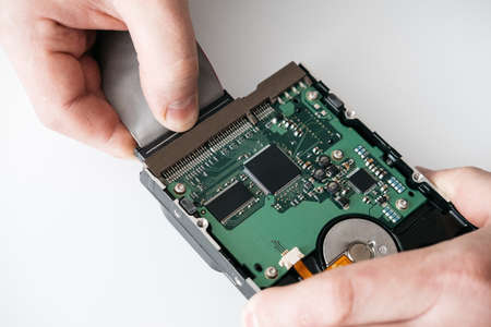 Hard disk recovery service, hands of repairman holding broken hdd with bad sectors. Computer engineer performs urgent repairs recovery of lost data during deletion HDD Banque d'images