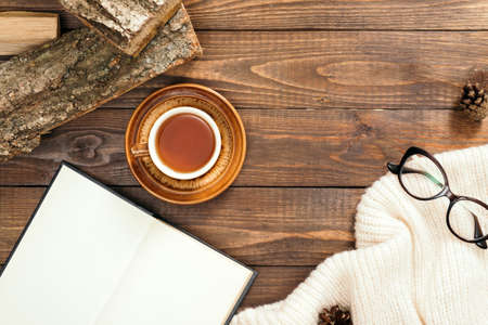 Hygge style flatlay composition with cup of tea, book with empty pages, white knitted scarf, woman glasses, firewood on wooden desk table. Autumn or winter holidays concept. Flat lay, top view.