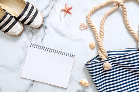 Women's beach accessories and blank notepad on marble background, summer holidays journey concept. Summer beach set: striped sandals and summer bag, seashells Standard-Bild