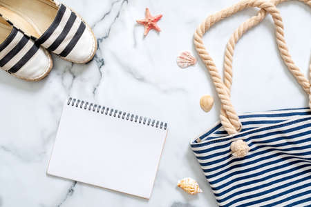 Women's beach accessories and blank notepad on marble background, summer holidays journey concept. Summer beach set: striped sandals and summer bag, seashells Imagens