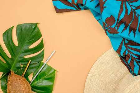 Tropical monstera leaves, coconut, drinking straws, straw hat and blue feminine dress on yellow background. Summer background, travel vacation, sea resort concept. Banner hero mockup for fashion blog
