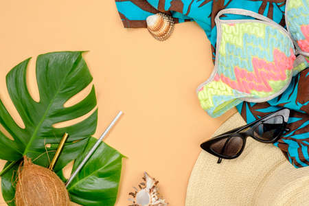 Tropical monstera leaves, coconut, drinking straws, feminine stuff and accessories on yellow background. Summer background, travel vacation, sea resort concept. Banner hero mockup for fashion blog
