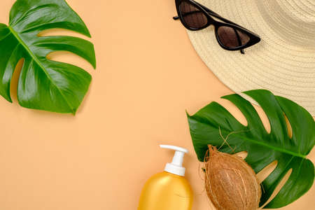 Flat lay stylish women clothes and accessories on yellow background. Top view topical monstera leaves, straw hat, coconut, suntan lotion. Summer background, copy space, banner mockup for fashion blog.