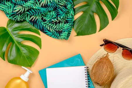 Flat lay traveler accessories on yellow background. Top view tropical monstera leaves, paper notepad, straw hat, sunglasses, coconut. Travel vacation concept. Frame set of traveler items.