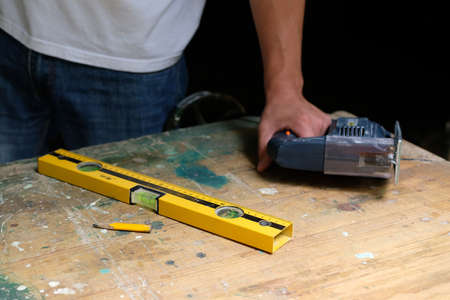 Hands of carpenter holding electric jigsaw lying on workbench with spirit level and yellow pen. DIY workwood concept.