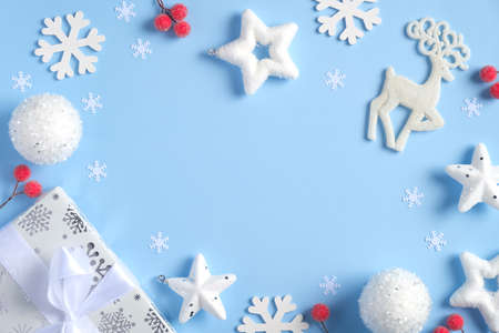 Christmas composition. Flat lay white snowflakes, gift box, Rudolph reindeer, confetti stars, red berries on blue background. Frame of Christmas decorations. Top view, copy space.