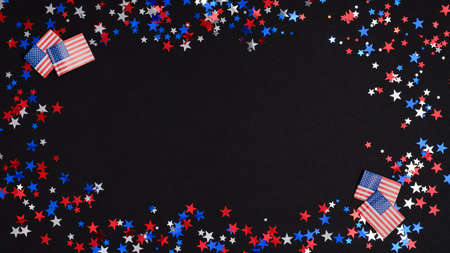 4th of July Independence day celebration background. Frame made of blue, red and white confetti stars and American flags on dark table. US national holidays concept.