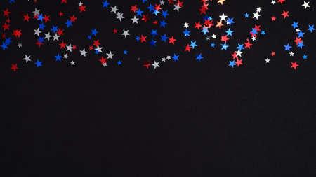 蓝、红、白五彩纸屑星星在黑色背景上的美国国家颜色。愉快的独立日横幅模板,7月4日庆祝概念。