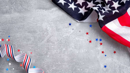 US American flags and confetti star on concrete stone background with copy space. Banner mockup for Presidents day, USA Memorial day, Veterans day, Labor day, or 4th of July celebration.