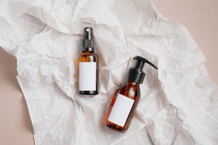 SPA natural organic cosmetics packaging in wrapping paper. Amber glass bottles mockups with white blank labels. Flat lay, top view. Stock Photo