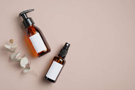 Amber glass cosmetic bottles and eucalyptus leaves on brown background. SPA bathroom natural cosmetic packaging mockup. Flat lay, top view.