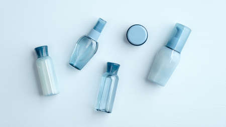 SPA natural organic cosmetic products set. Top view water based skincare beauty products on blue background. Flat lay blue transparent plastic bottles with shampoo, body lotions, cream.