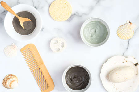 Face clay masks in bowls with hair comb, loofah sponge, homemade soap and seashells on marble background. Flat lay, top view. SPA natural organic cosmetics for face treatment, skin care