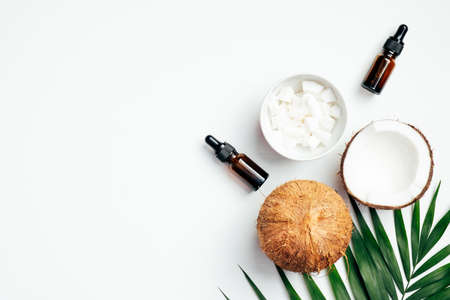 Natural coconut essential oil for hair care with palm leaf and coconuts on white background. SPA organic cosmetic, health and beauty concept. Flat lay, top view