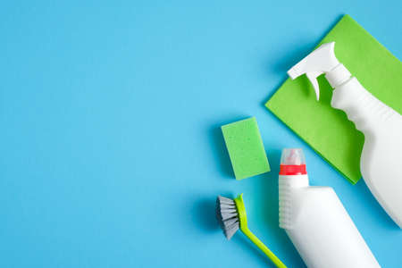 House cleaning supplies on blue background. Cleaning service and housekeeping concept. Flat lay spray bottle, sponge, rag, brush and cleaning detergent.
