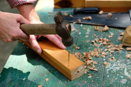 Carpenter with hammer hitting nails.Woodwork concept.
