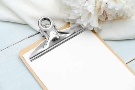 Blank paper clipboard mockup with white peony flowers on blue wooden table. Top view. Wedding planner, to do list, checklist concept.