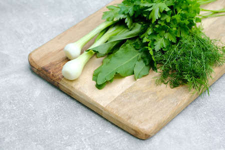 Fresh raw healthy organic food, salad ingredients on wooden cutting board. Top view green onion, parsley, dill, sorrel