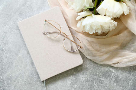 Flat lay composition with paper notebook, glasses, bouquet of peonies flowers and beige fabric on concrete table. Top view stylish feminine workspace.