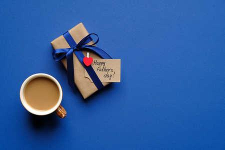 父亲节理念快乐。平铺构图与复古礼盒包装的蓝色丝带和一杯咖啡在蓝色的背景。父亲节卡片模板,横幅模型。