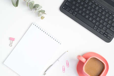Stylish office table desk. Feminine workspace with laptop computer, paper notepad, pink coffee cup and clips on white background. Flat lay, top view